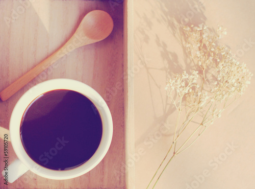 Black coffee and spoon on wooden tray with dried flower, retro f