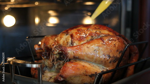 Basting a Seasoned Whole Turkey with Melted Butter