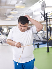 overweight man measuring his big belly in gym