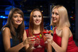 three girls raised their glasses in a nightclub