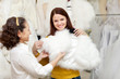 happy women chooses bridal outfit at wedding store
