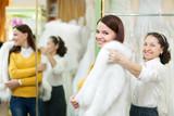 woman helps the bride in choosing fur cape