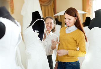pretty bride chooses bridal outfit at wedding store