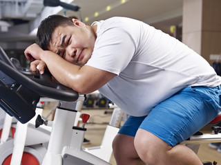 overweight man exhausted in gym