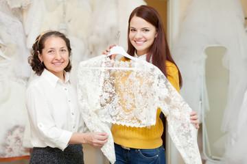 Happy mature bridesmaid with bride chooses bridal clothes