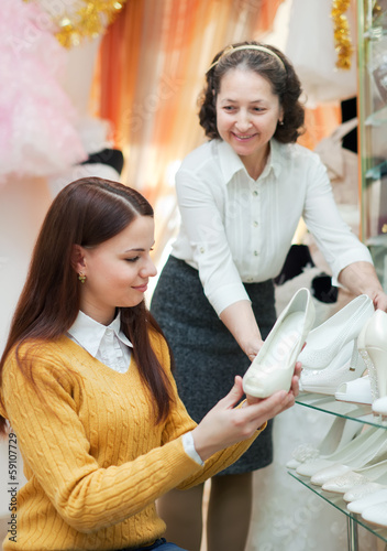 women chooses white shoes at shop