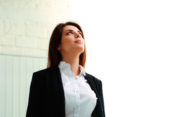 Young businesswoman looking up at copyspace in office