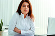 Young thoughtful businesswoman sitting at the table in office