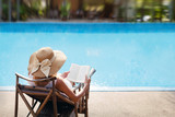 Fototapety woman reading and relaxing near luxury swimming pool