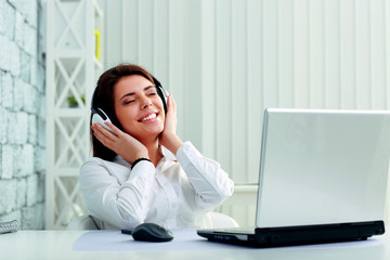 Young cheerful businesswoman listening music