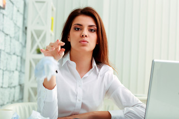 Young frustrated businesswoman throwing paper in camera