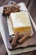 Rustic wooden cutting board with a honeycomb and cinnamon sticks