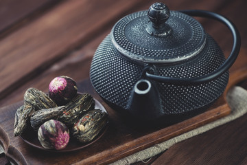 Cast-iron teapot and variety of compressed tea, horizontal shot