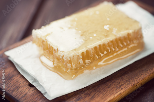 Close-up of a golden honeycomb, rustic wooden background