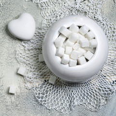 bowl with white lump sugar on wooden table with crochet doily