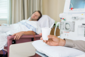 Cancer Patient Holding Glass Of Crushed Ice