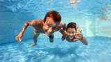 Underwater brothers portrait in swimming pool.