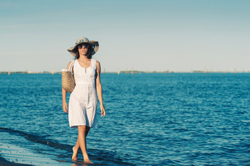 Young woman wearing white dress walking at the beach.