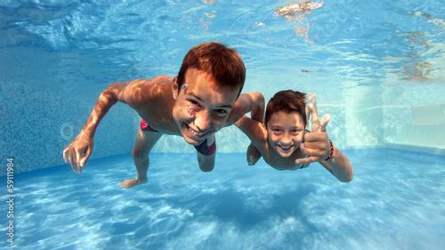 Leinwanddruck Bild Underwater brothers portrait in swimming pool.