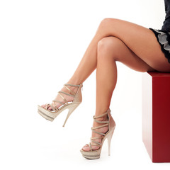 Sexy young woman legs with high hells shoes on white background.