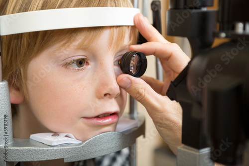 Optician's Hand Examining Boy's Retina