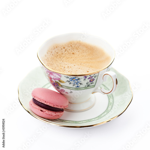 Pink macaroon on a saucer with cup of coffee