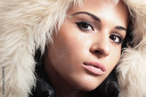 young beautiful woman in fur hood. winter style. tender