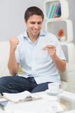Smiling man paying his bills at home