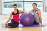 Young woman and man with fitness ball sitting at gym - 59114980