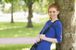 Cute redhead student leaning against a tree