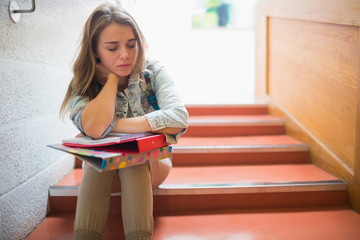 Upset student sitting on stairs