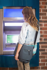 Student standing at the atm