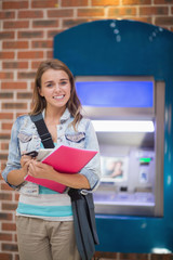 Pretty student standing smiling at camera at the atm