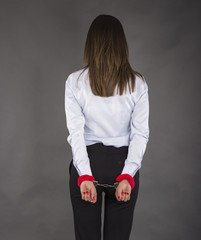 Female businesswoman with handcuffs on gray