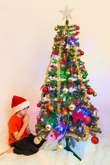 Child praying in front of a Chrismas Tree