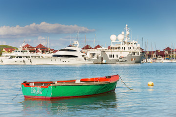 Fishing boat with luxurious yachts background, Eden Island, Mah