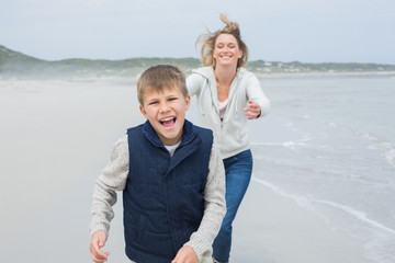 Woman and cheerful boy running at beach
