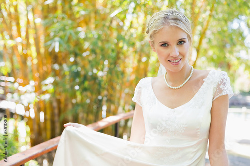 Smiling blonde bride in pearl necklace looking at camera © lightwavemedia