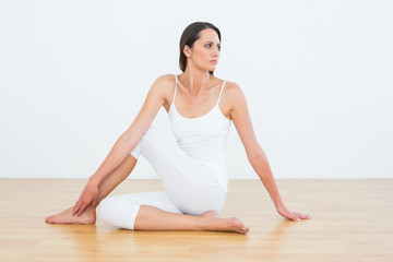 Fit woman doing the half spinal twist pose in fitness studio