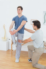 Male therapist assisting young man with stretching exercises