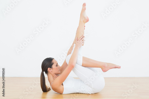 Fit woman stretching body in fitness studio