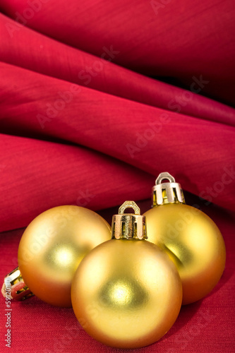 golden christmas ball on a red silk cloth