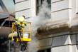 Leinwanddruck Bild - a worker washes the facade
