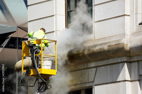 Leinwanddruck Bild a worker washes the facade