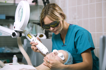 Woman undergoing laser skin treatment