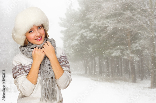Young woman in fur hat at forest
