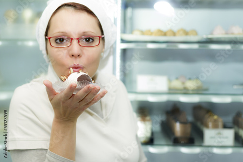 Woman with pastry in hand in Ice Cream store