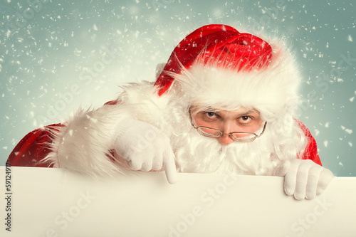 Fototapeta Santa Claus in a snow pointing to white blank banner