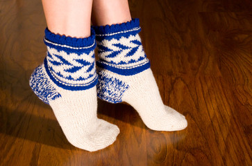 Feet warm socks on dark wooden floor