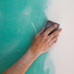 plastering man hand sanding the plaste in drywall seam